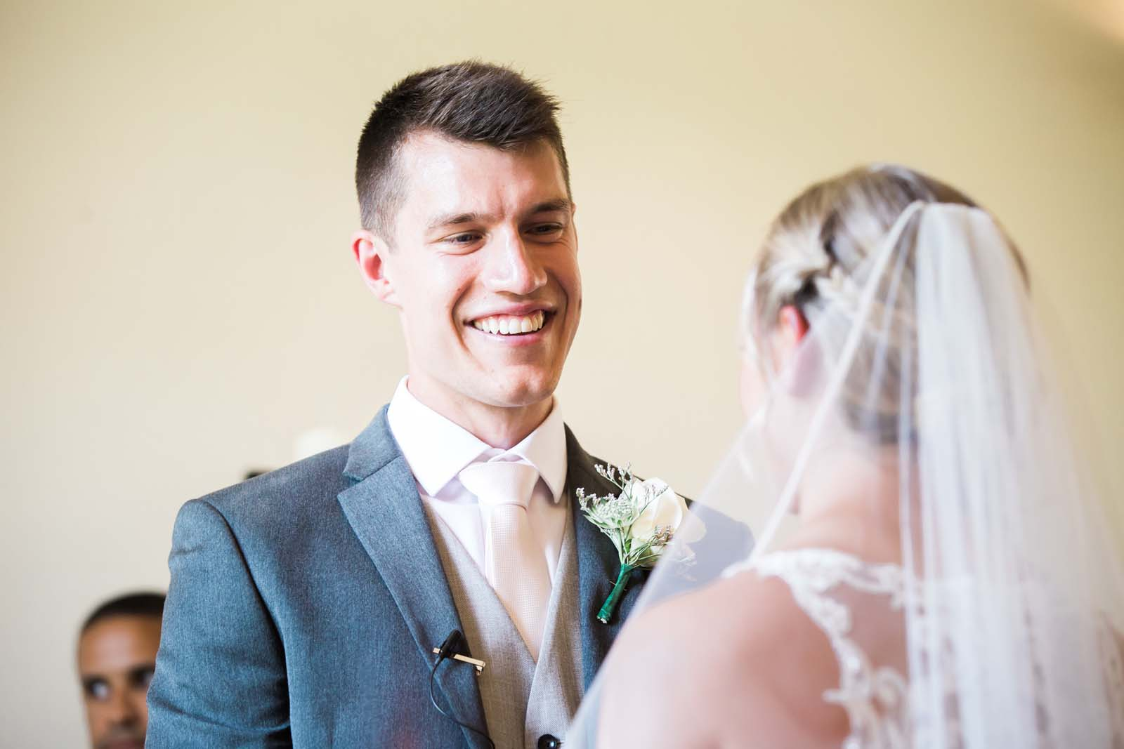 Notley Abbey wedding in Buckinghamshire handsome groom smile lovingly at his bride