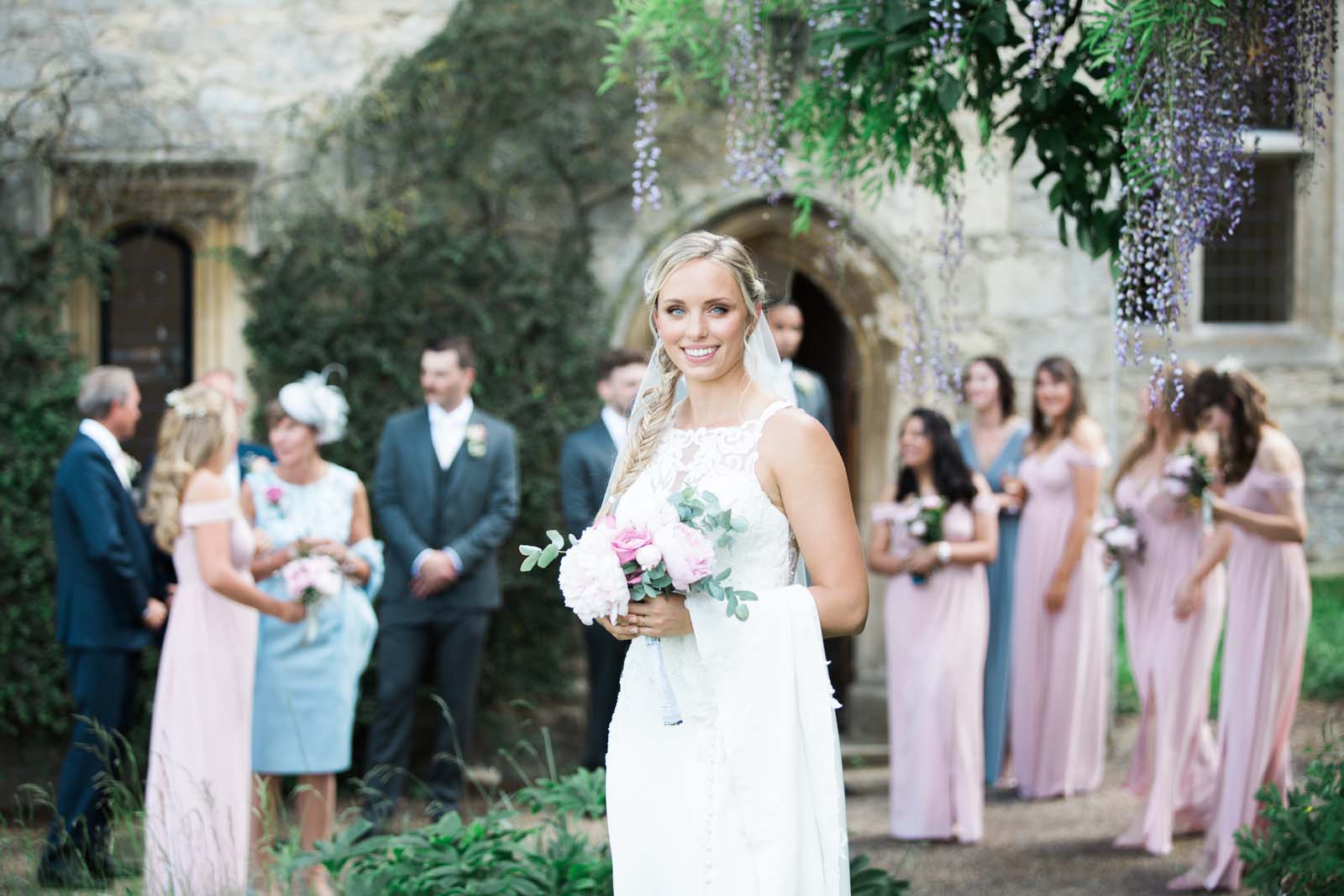 Notley Abbey Wedding Buckinghamshire Bride with Wedding Party in the background