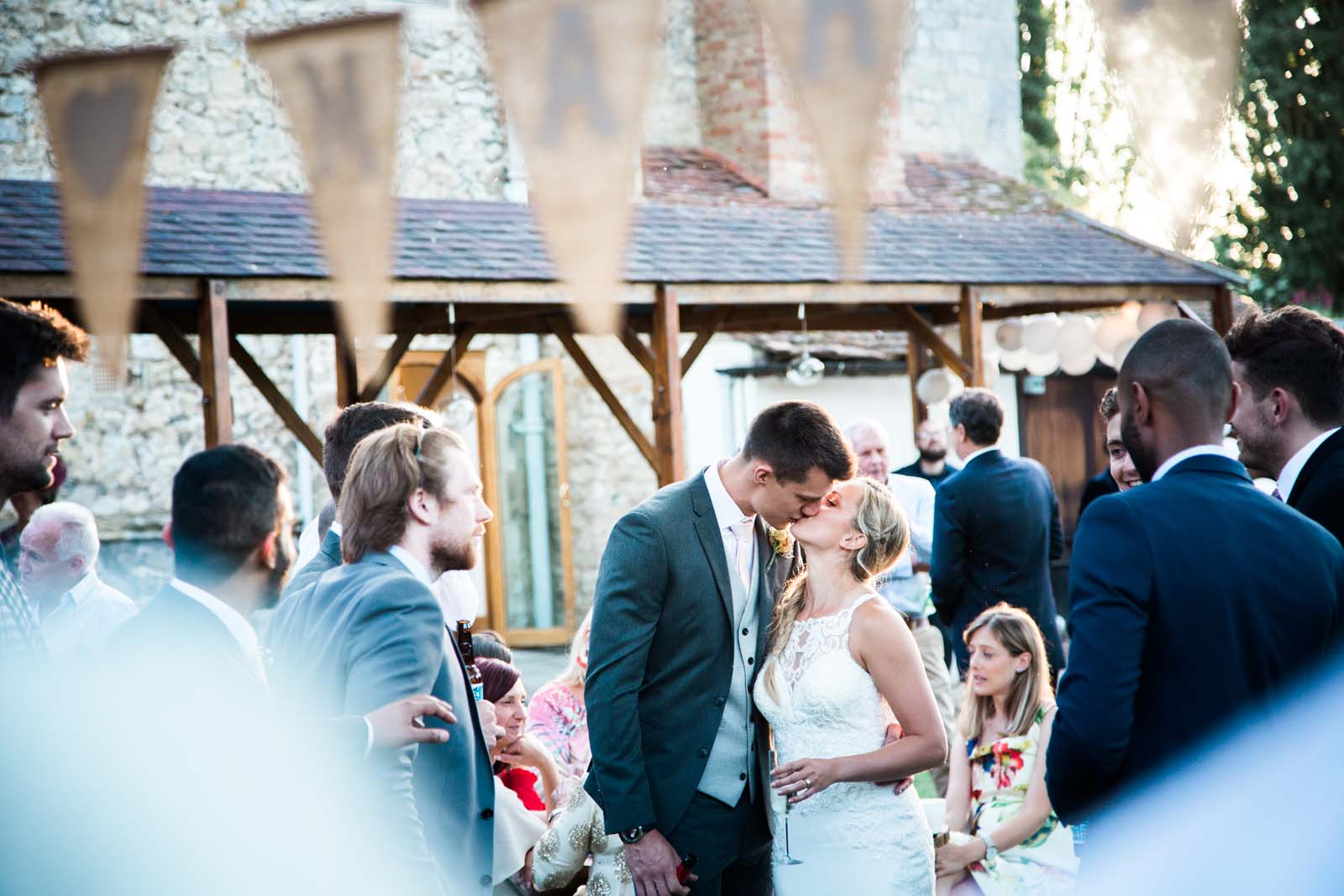 Notley Abbey Romantic Kiss Underneath Bunting Wedding Buckinghamshire
