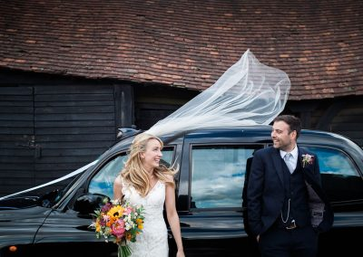 Creative Wedding Photography - Happy Couple Veil Blowing in Wind